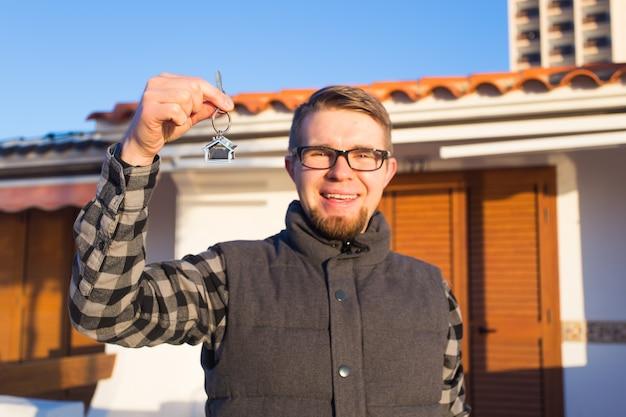 Концепция собственности, владения, нового дома и людей - молодой человек с ключами стоит возле нового дома