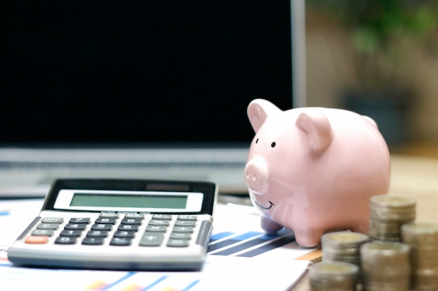 Property or real estate investment concept.laptop, stack of coins and piggy bank on table