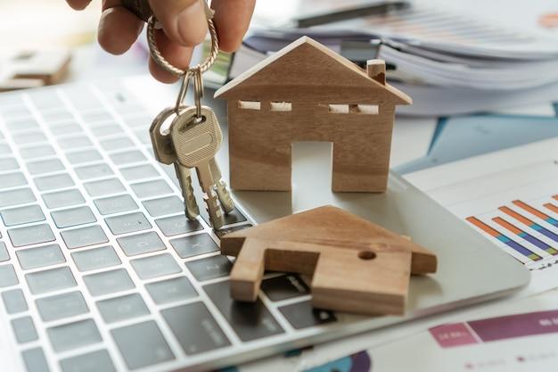 不動産の住宅ローンまたは投資の概念:サインエリアメント契約および保険のために顧客にキーハウスを与える販売代理店によるチャートレポート文書を備えたコンピューター上の木製住宅モデル