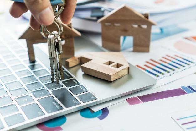 Ипотечная ссуда на недвижимость или инвестиционная концепция: модель деревянного дома на компьютере с отчетными документами диаграммы агентом по продажам, который передает клиенту ключевой дом для подписания договора аренды и страхования