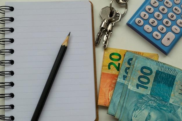 不動産賃貸計画。ブラジルのお金、電卓、メモ帳、鉛筆、鍵。