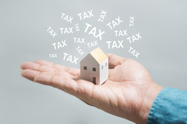 Property tax concept with hand holding house toy