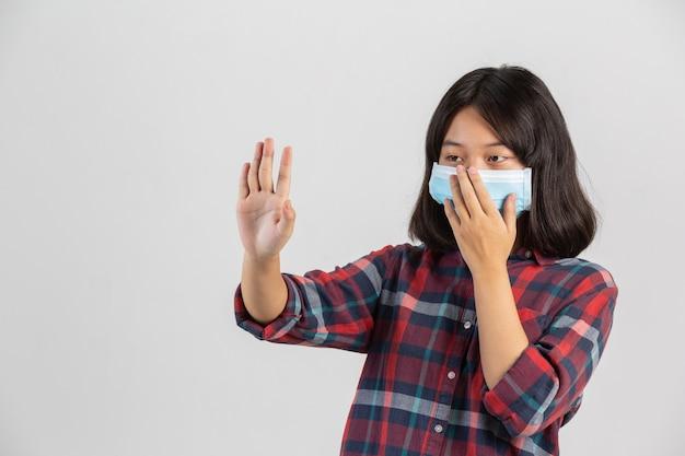 Милая девушка носит маску и делает руку стопа от другого prople на белой стене.