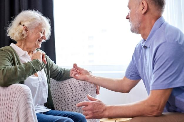提案。提案をしている年配の男性と笑顔の幸せな女性、灰色のひげを生やした男性は、自宅で妻に金の指輪を与えます