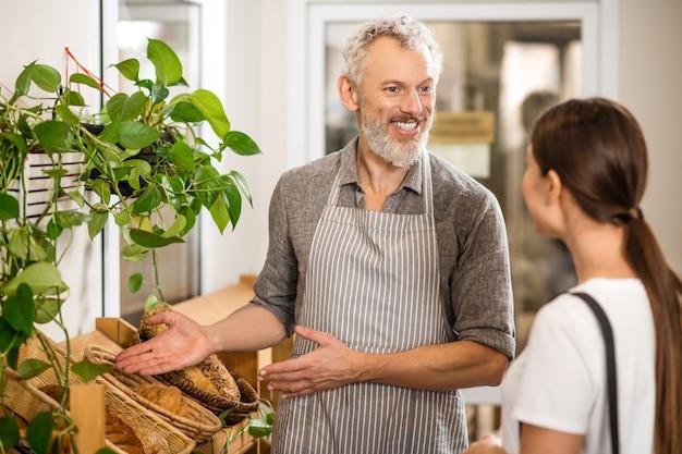 提案。背中を持って立っている顧客に手で優しく身振りで示すベーカリー製品を提供するエプロンで笑顔の白髪の男