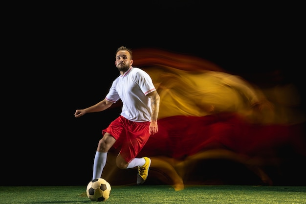 Propose. young caucasian male football or soccer player in sportwear and boots kicking ball for the goal in mixed light on dark wall. concept of healthy lifestyle, professional sport, hobby.