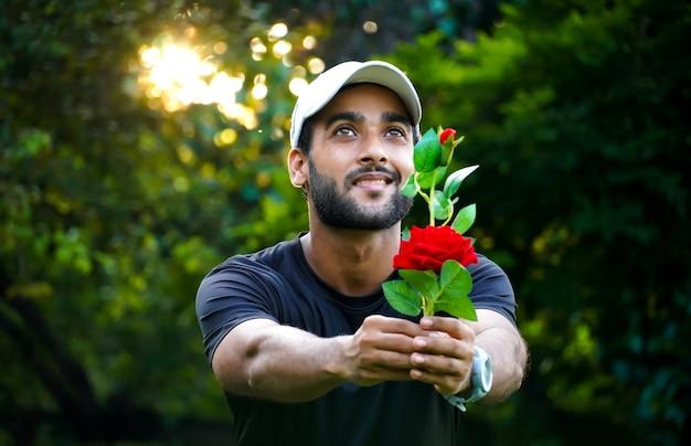 Делает предложение своей девушке мужчина с красивой красной розой, дающий девушке