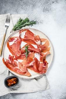 Prosciutto crudo, italian salami, parma ham. antipasto plate. gray background, top view, space for text