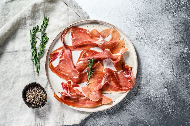 Prosciutto crudo, italian salami, parma ham. antipasto plate. gray background, top view, space for text