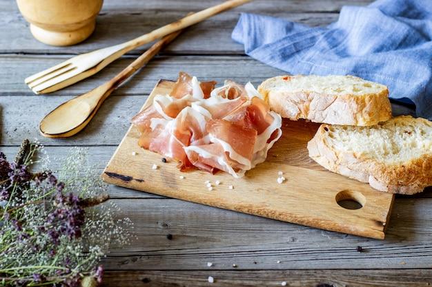 Prosciutto ham and bread on wood