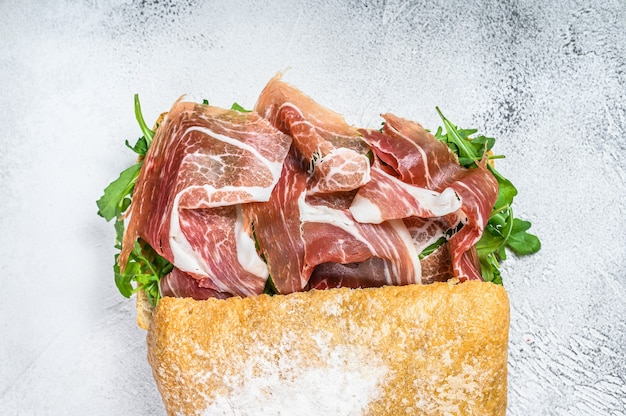 Prosciutto parma ham sandwich on ciabatta bread with arugula. white table. top view.