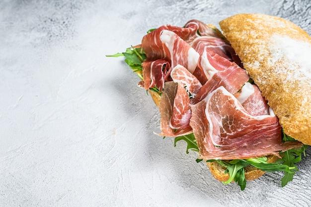 Бутерброд с ветчиной прошутто и пармской ветчиной на хлебе чиабатта с рукколой.