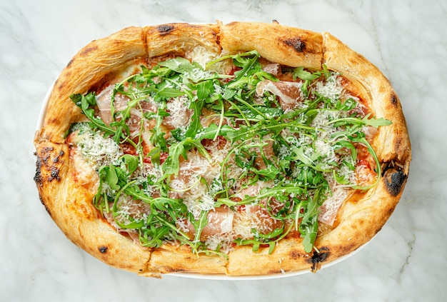 Prosciutto pizza or pinza with arugula in roman style on marble surface
