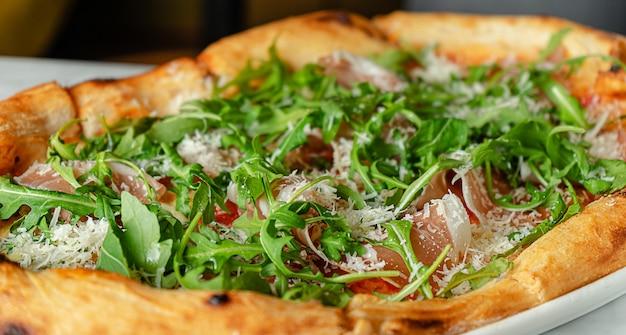 Prosciutto pizza with arugula in roman style, italian cuisine
