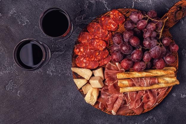 Prosciutto, sausage, wine, grape, parmesan on dark table