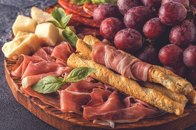 Прошутто, колбаса, вино, виноград, пармезан на темном столе