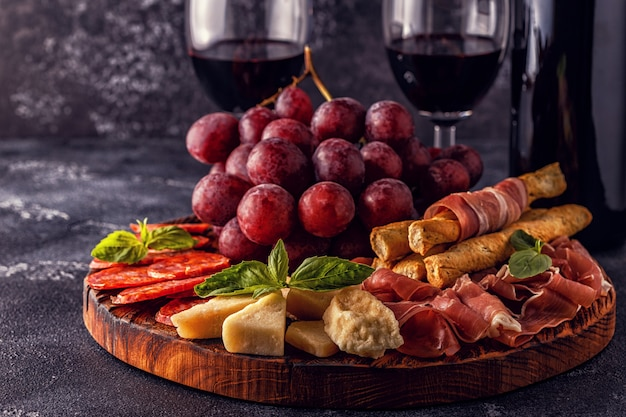 Prosciutto and sausages with cheese and grapes