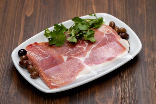 Прошутто с оливками и петрушкой на белом блюде на деревянной поверхности