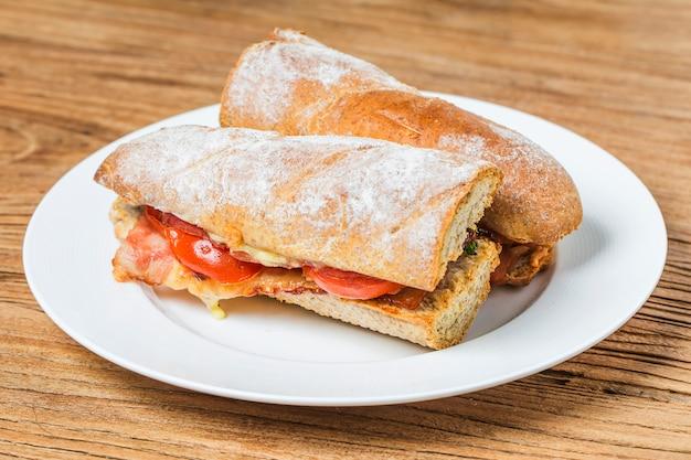 キッチンテーブル、浅いフォーカスにprosciutto、モッツァレラ、トマトとオープンサンドイッチ