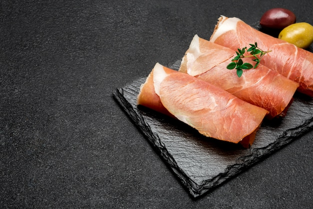 Proscuitto ham arranged in thinly sliced rolls on stone serving board