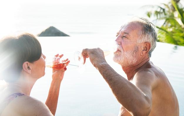 スイミングプールでproseccoを飲むシニアカップル