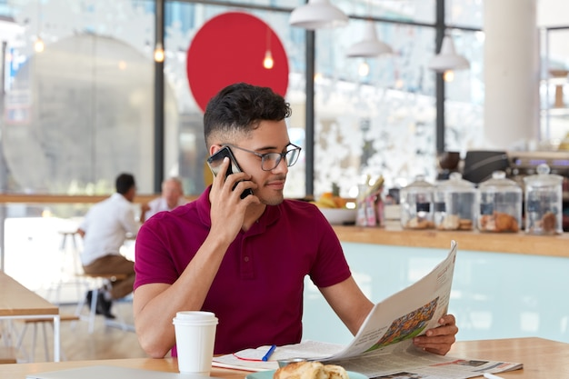 Prosperous attractive businessman writes latest issue of newspaper, focused on interesting publication during coffee break, discusses something with partner via cell phone, writes in notebook