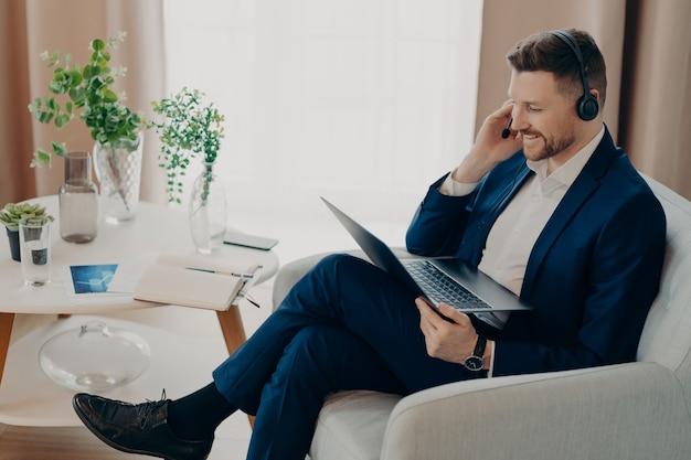 노트북 컴퓨터 화면에 집중하는 수염 난 남성 기업 직원은 성장 전략을 개발하여 정장 차림의 화상 통화를 넓은 거실의 편안한 안락의자에 앉힙니다