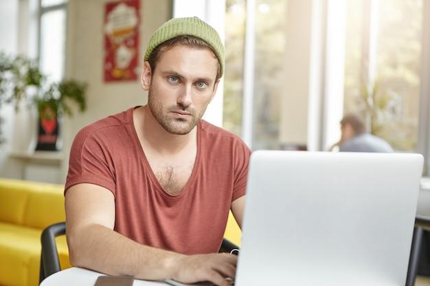 裕福な若いマネージャーはカジュアルなtシャツと帽子をかぶって、一般的なラップトップで作業します