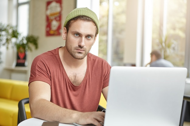 Il giovane manager prospero indossa una maglietta e un cappello casual, lavora su un laptop generico