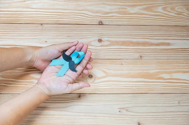 Prostate cancer awareness, hand holding light blue ribbon