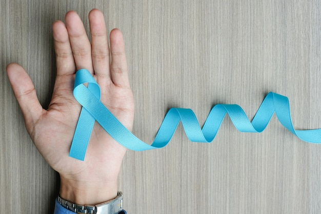 Prostate cancer awareness, man hand holding light blue ribbon