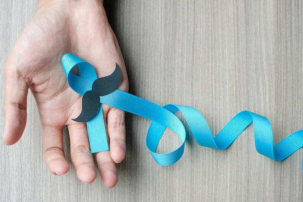 Prostate cancer awareness, man hand holding light blue ribbon