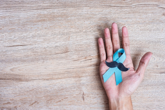 Prostate cancer awareness, man holding light blue ribbon with mustache