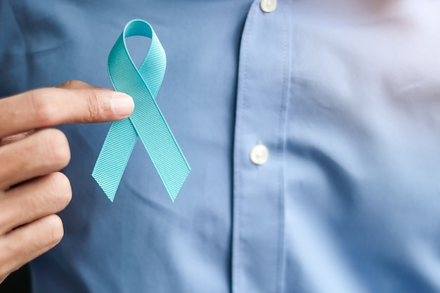 Prostate cancer awareness, man holding light blue ribbon