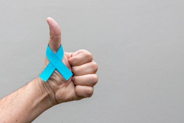 전립선 암 예방 캠페인 블루 11 월 긍정적 인 기호로 손가락에 파란색 리본 활