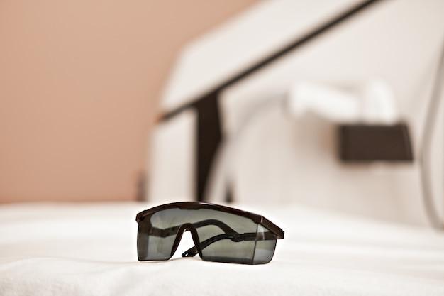 目の上の眼鏡と背景の皮膚治療のための美容装置を保護します。ビューティースパサロン。