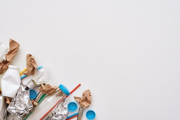 環境を守れ。しわくちゃのホイル、紙、プラスチックが隔離された床に横たわっています。左隅に分別されていないさまざまな種類のゴミの写真