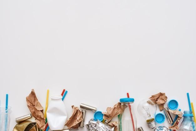 環境を守れ。しわくちゃのホイル、紙、プラスチックが隔離された床に横たわっています。分類されていないさまざまな種類のゴミの写真