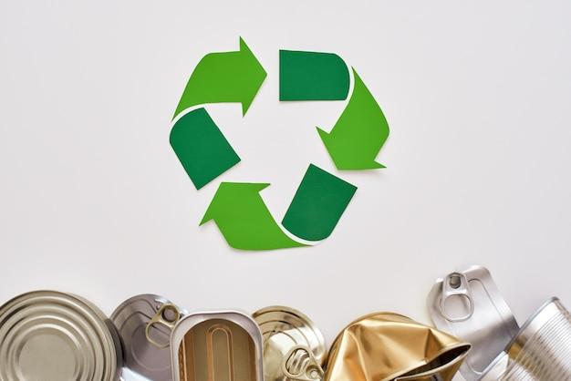 環境を守れ。しわくちゃの缶詰商品がリサイクルシンボルの近くにあります。未分類の金属ごみ