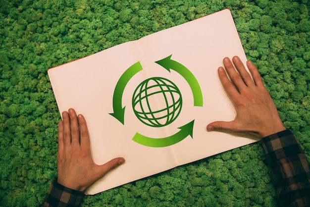 환경을 보호하다. 이끼 배경에 화살표와 행성 기호가 있는 노트북에 손을 잡고 있는 남자의 상위 뷰 클로즈업 이미지