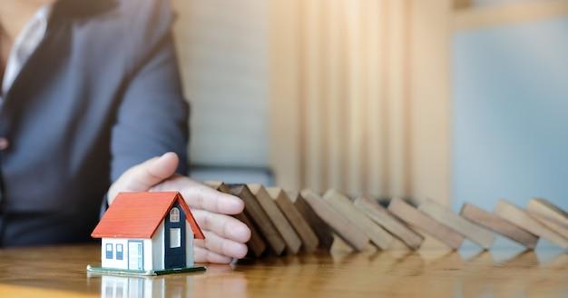 Защитите дом от падения деревянных блоков, страхования и риска концепции.