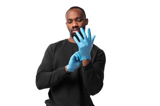 お肌を守ります。コロナウイルスが私たちの生活をどのように変えたか。白い壁に保護手袋を着用している男。肺炎の予防、検疫を続け、家にいる。治療covid、回復。