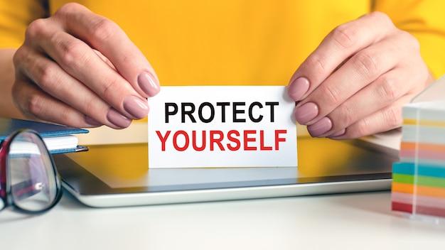 자신을 보호하는 것은 여성의 손에 든 흰색 명함에 쓰여 있습니다. 노란색 배경. 안경, 태블릿 및 메모 용 멀티 컬러 종이 블록. 비즈니스, 광고 개념에 사용할 수 있습니다.