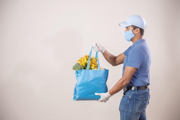 保護された配達人が果物と野菜で生態学的バッグをロード