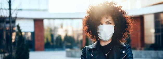 巻き毛の保護された女性は、カメラを見て、特別な白いマスクを身に着けている間、晴れた日にポーズをとっています