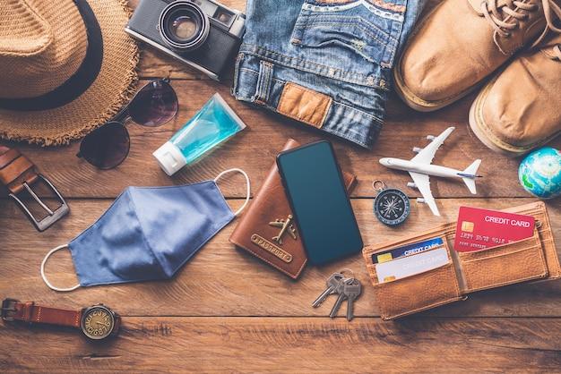 Защита от covid-19 во время путешествий. костюмы для путешествий. паспорта, багаж, стоимость туристических карт, подготовленных к поездке. концепция нового нормального образа жизни.