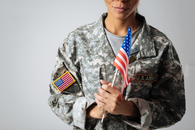 Protecting everything i love. confident strong marvelous woman wearing a uniform and holding a flag in her hands