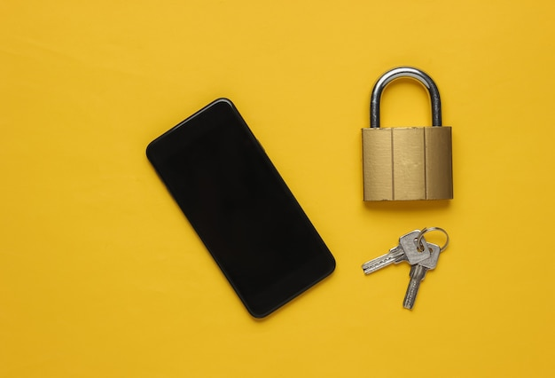 Protecting your smartphones personal data smartphone with keys lock on yellow background