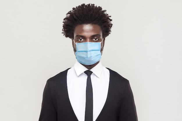 전염병, 코로나바이러스에 대한 보호. 감염을 예방하기 위해 위생 마스크를 쓴 남자, 독감, 코비드-19와 같은 공기 중 호흡기 질환. 회색 배경에 고립 된 실내 스튜디오 촬영