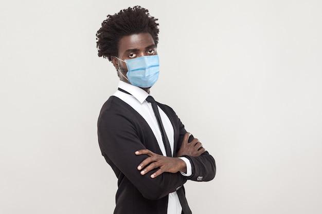 コロナウイルスに対する保護。感染を防ぐために衛生マスクを着用している一人の男、covid-19。腕を組んで、悲しい心配顔でカメラを見てください。灰色の背景に分離された屋内スタジオショット